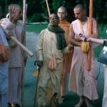 05 Прабхупада с цветком в руке что-то рассказывает преданным